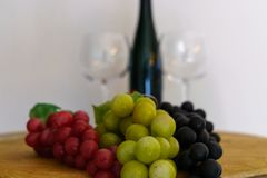 Grapes and a wine bottle on an oak barrel stock photo