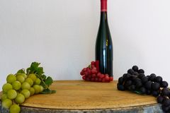 Grapes and a wine bottle on an oak barrel. Green grapes and a wine bottle on an old oak barrel stock images