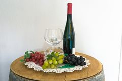 Grapes and a wine bottle on an oak barrel. Green grapes and a wine bottle on an old oak barrel royalty free stock images