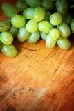 Green grapes. On wooden background Royalty Free Stock Photo