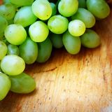 Green grapes. On wooden background Royalty Free Stock Photos