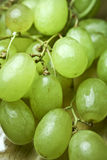 Green Grapes on a Wooden Table. Green grapes rinsed and set on a kitchen table Royalty Free Stock Image