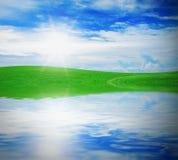 Green grass against a blue sunny sky Stock Photo
