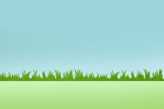 Green grass background with blue sky. Plastic green grass on artificial blue sky with blurry backgorund Stock Photos