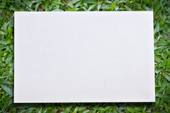 Green grass background with white paper Royalty Free Stock Photography