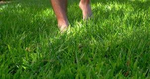 Green grass with barefoot man walking through