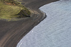 Green grass, black sand and blue water in Iceland Stock Photo