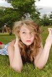 Green grass blue eyed beauty. Girl on grass with messy hair, read lips and blue eyes Royalty Free Stock Photos
