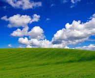 Green grass and blue sky. Brilliant green grassy hill against an equally brilliant blue sky with fluffy white clouds. Taken at Conder Green, Lancashire, U.K Stock Photos