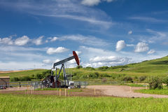 Green grass, blue sky and pumpjack. Beautiful landscape with green grass, blue sky and pumpjack. Photo was taken on sunny day of summer in Alberta, Canada Royalty Free Stock Images