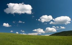 Green grass blue sky and white clouds. Beautiful european summer landscape with white clouds stock image