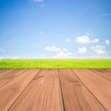 Green grass with blue sky and wood floor background. Field of green grass and sky Stock Image
