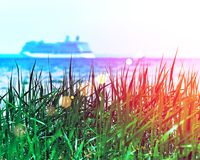 Green grass with a blurried unfocused cruise ship sailing away on sunset horizon. Vacation conception. RGB toned with a colorful l. Ens flare Stock Image