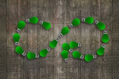 Green grass bulbs, infinity symbol, ECO circular economy. Light bulbs with green grass in form of arrow infinity recycling symbol, on dark wooden wall background royalty free stock images
