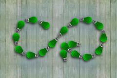 Green grass bulbs, infinity symbol, ECO circular economy. Light bulbs with green grass in form of arrow infinity recycling symbol, on green wooden wall royalty free stock photography