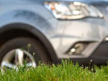 Green grass with car staying on background. Car staying on green grass background Royalty Free Stock Photo