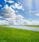 Green grass and cloudy sky Stock Image