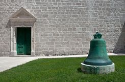 Church bell and wall - green and white. Green grass and green corroded copper church bell in the front of limestone facade wall and marble framed church door royalty free stock photography