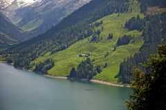 Green Grass Covered Mountain Beside Blue Body of Water Royalty Free Stock Photo