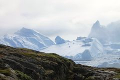 Green Grass Covered Mountain Next to Snow Covered Mountain during Daytime Stock Photos