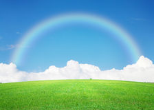 Green grass field, blue sky with clouds on horizon and rainbow Royalty Free Stock Image