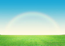 Green grass field and deep blue sky with rainbow Royalty Free Stock Image