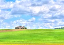 Green grass field landscape under blue sky and clouds. With rural house in the background Stock Photo