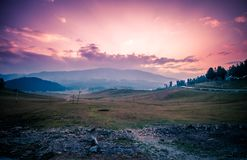 Green Grass Field Near Mountains Under Golden Hour royalty free stock photography