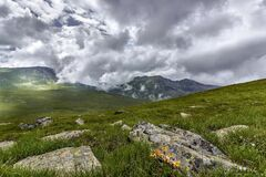 Green Grass Field With Rocks Near Mountains during Cloudy Daytime Sky Royalty Free Stock Photography