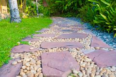 Green grass field with stone pathway and small rock decoration. Nature background Stock Photography