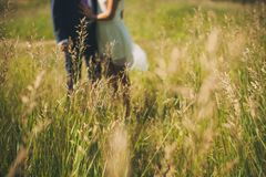 Green grass in the field on a Sunny summer day, in the background are blurred guy and girl, newlyweds. The groom in a classic suit royalty free stock image