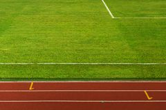 Green grass field texture for sport and soccer or football with red brown white line running lane background. Green grass field texture for sport exercise and stock image