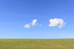 Green grass field and tiny cloud in blue sky. Royalty Free Stock Photos