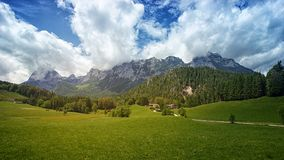 Green Grass Field With Trees and Mountain in Background Under Cloudy Sky royalty free stock images