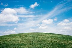 Green Grass Field Under White Clouds royalty free stock image