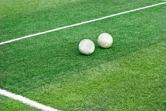 Green grass field with white mark line and two old football soccer Stock Image