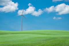 Green grass field with wind turbine for alternative energy blue Stock Photos