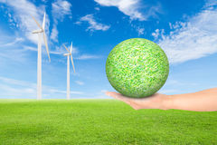 Green grass field with wind turbine and hand holding green grass. Ball against blue sky background,used for green earth concept Stock Photo