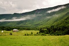 Green Grass Fields Beside Green Mountains Under White Sky during Daytime Royalty Free Stock Photos