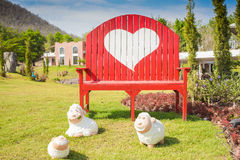 Green grass and heart shape on bench Stock Photos