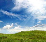 Green grass hill. Landscape with green grass hill under blue sky Stock Photo
