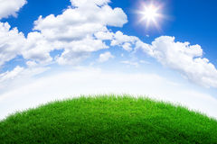 Green grass hill. And cloudy blue sky Royalty Free Stock Images