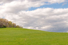 Green grass hill in Springtime with clouds. Upstate rural New York Royalty Free Stock Photo