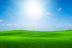 Green grass hills landscape with blue sky summer. Green grass hills landscape in summer against blue sky and white clouds. Sun shines on grass hills creating royalty free stock images