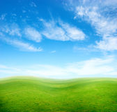 Green grass hills under blue sky. Royalty Free Stock Photography
