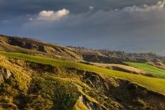 Green grass hills under dark clouds Stock Photos