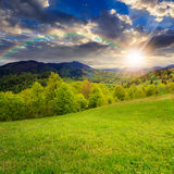 Green grass on hillside meadow in mountain at sunset. Summer landscape. rainbow ower the green grass on  hillside meadow. forest in fog on the mountain at sunset Stock Photos