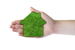 Green grass home icon in his hand. Abstract green grass house on over white background. Ecology concept stock image