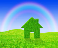 Green grass house symbol. With rainbow on meadow Stock Photo