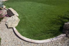 Green Grass Lawn with Stones and Rocks Stock Images